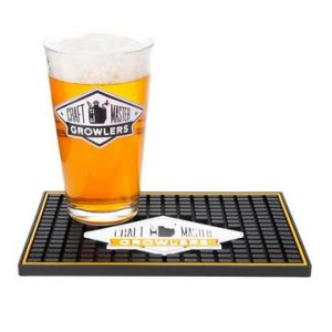 A bar mat with a pint glass full of beer on it.