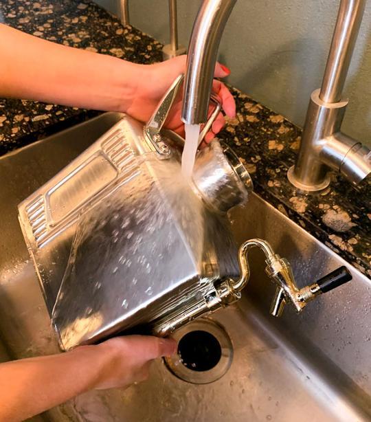 washing a pressurized growler under warm water.